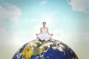 woman meditating on top of Earth