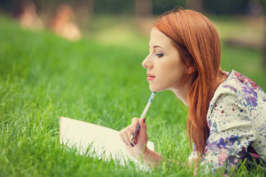 woman writing in grass