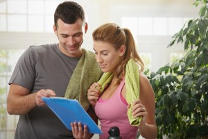 man and woman in gym looking at exercise plan