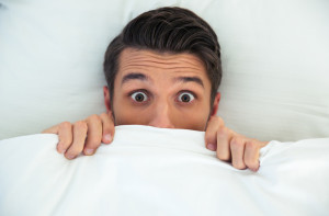 man hiding under covers