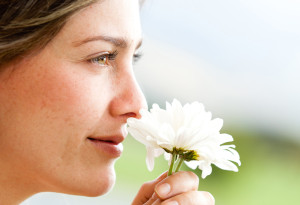 woman sniffing daisy flower