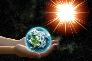 hands holding planet Earth in sunlight