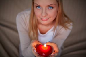 woman holding heart-shaped candle in her hands