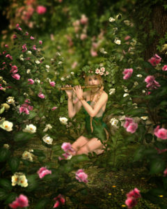 fairy playing flute among flowers