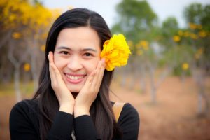 smiling woman with yellow flower