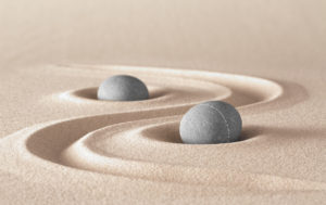 Two stones in swirls of sand. Peaceful, energetic, vitality, health, focus, zen, meditation, being free of the ego.