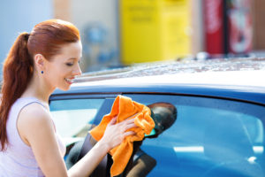 Woman cleaning windshield. Clarity, relief, calming.