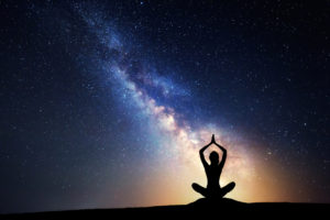 person meditating silhouetted in front of Milky Way galaxy with a soft golden aura around them