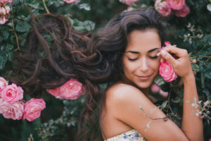 Peaceful woman with roses. True self, connecting with nature, natural humanity.