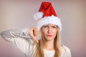 Annoyed-looking woman in Santa hat giving a thumbs-down. Holiday distress, Christmas boredom.