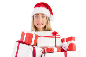 Holiday overwhelm and stress too much to deal with? (Frantic looking woman under huge load of wrapped presents.)