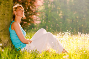 Woman leaning against tree looking peaceful and in harmony. Natural alignment.