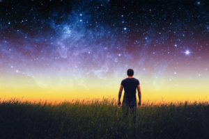 Empowered man standing in field looking up at beautiful universe sky.