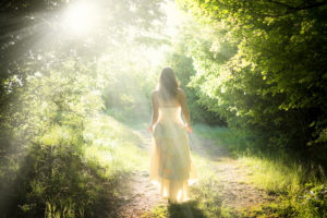How can you be a lightworker on a practical level? Woman walking down sunlit path in nature.