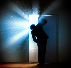 Man in dark room opening door to let in brilliant light
