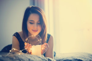 What is a lightworker? Woman peacefully contemplating with candle.
