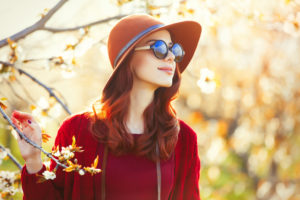optimistic, smiling woman by blossoming tree