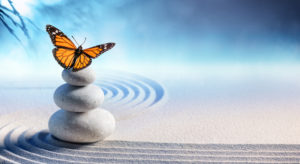 butterfly atop stack of Zen pebbles